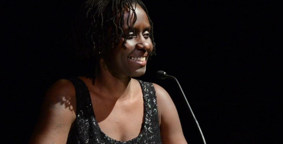 Juliane Okot Bitek onstage with a microphone