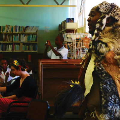 Moroka Moreri wears fur and patterned clothes, performing poetry in a room full of books