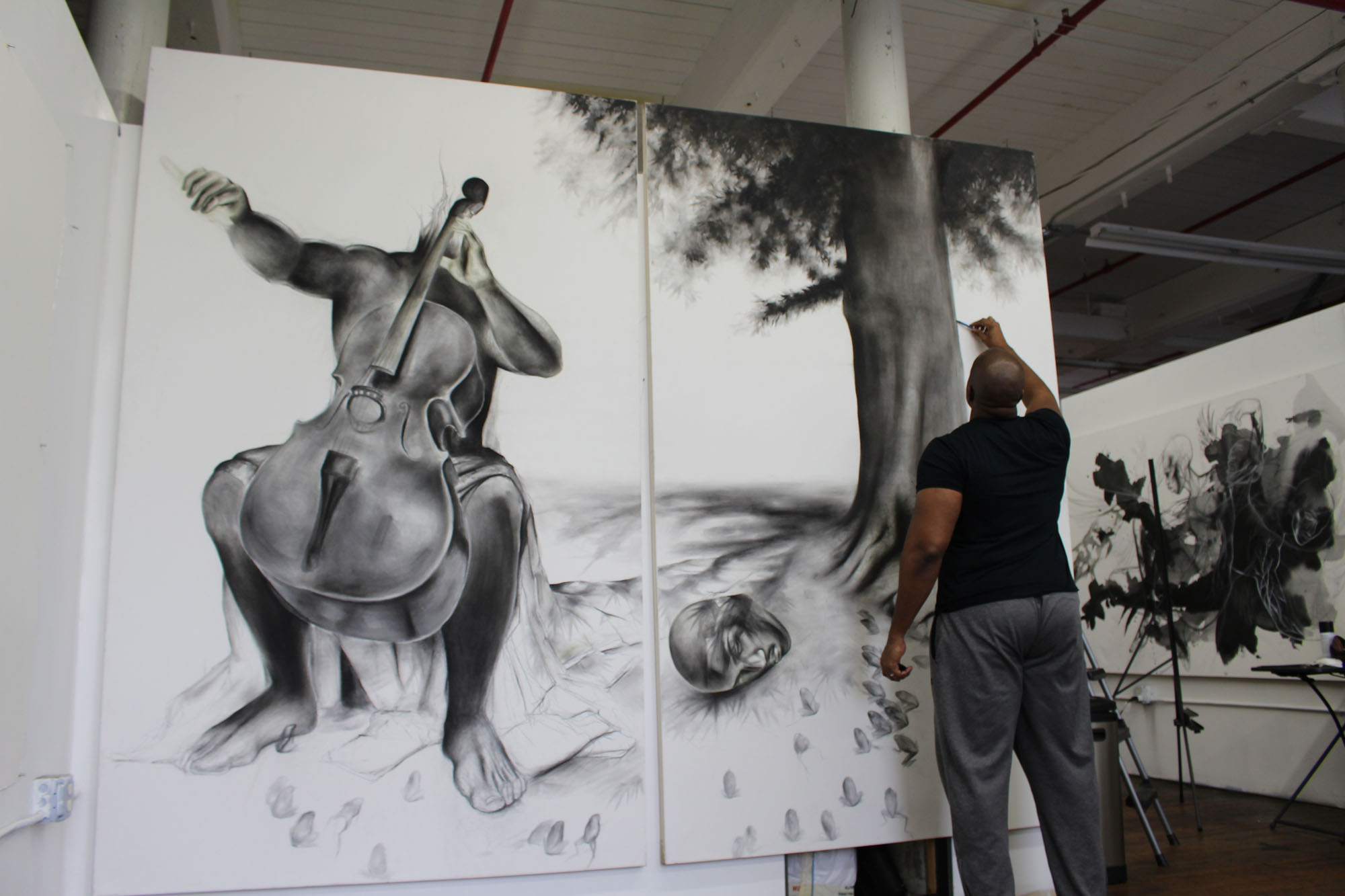 Artist Imo Imeh Nseh stands in front of a tall double canvas painting in black and white